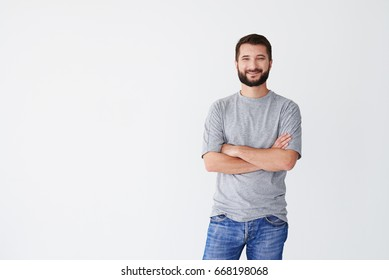 Cheerful man of middle age against white background, having arms folded on chest, wearing jeans and T-shirt, mid shot