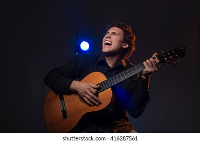Cheerful man playing on guitar over dark background