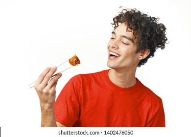 Cheerful man in a red T-shirt holding chopsticks sushi rolls fast food