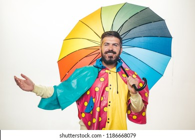 Cheerful man rejoices in autumn sales. Young attractive man in raincoat under colored umbrella is he trying to see if there is rain. Autumn discounts on clothes. Sale of men's underwear