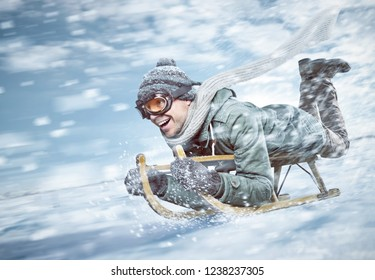 Cheerful man sledding down a snowy slope in full speed