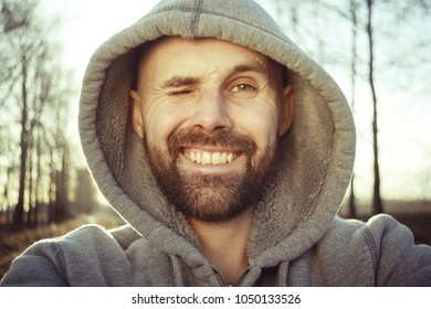 cheerful man with  smile,  bearded guy looks at the camera and laughs, a bright spring smile of a man