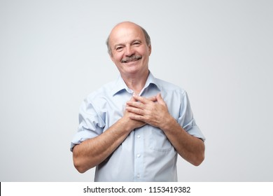 Cheerful man smiles happily, keeps hands on chest, expresses his positive emotions, poses against gray studio background. Pleased male glad to recieve compliment from woman.