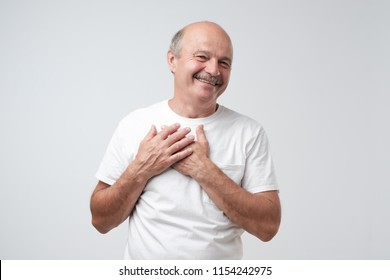Cheerful man smiles happily, keeps hands on chest. Pleased male glad to recieve compliment from woman.