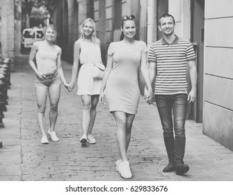 Cheerful man and smiling beautiful woman taking promenade in european town on summer day