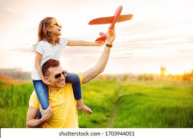 Fröhlicher Mann lächelt und trägt aufgeregtes Mädchen auf Schultern, während er mit roten Flugzeugen zusammen gegen bewölkten Himmel an sonnigen Sommertagen spielt