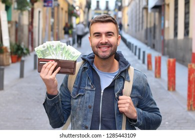 Cheerful man with some cash in his wallet