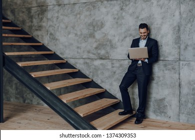 Cheerful man in suit is standing and holding laptop. He is looking at screen with joy while staying on stairwell