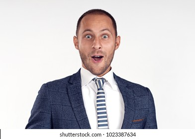 A cheerful man in a suit with a tie is surprised. White background. Isolated image. Portrait of a surprised young man smiling.