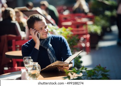Cheerful man take a call with his smartphone while reading menu at outdoors cafe