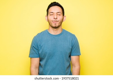 Cheerful man thinking about eating a delicious lunch with his eyes closed. Handsome man in his 30s licking his lips and craving a tasty dinner