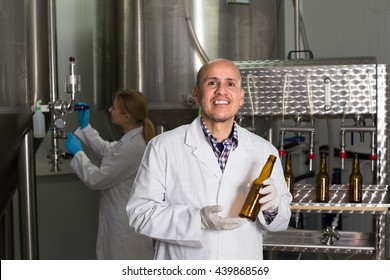 Cheerful man in white uniform using bottling equipment on brewery