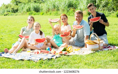 Cheerful man and woman with four kids having watermelon on picnic together