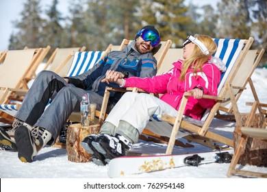Cheerful man and woman in love sunbathing in sun lounger on skiing