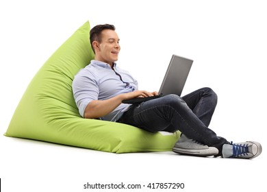 Cheerful man working on laptop seated on a green beanbag isolated on white background
