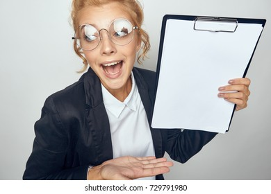 cheerful manager woman with glasses holds a folder with a white sheet of paper on a gray background portrait