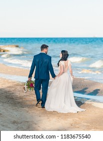 Cheerful married couple at wedding Day on the beach near the sea. Smiling bride and groom. Young couple in love. Back view