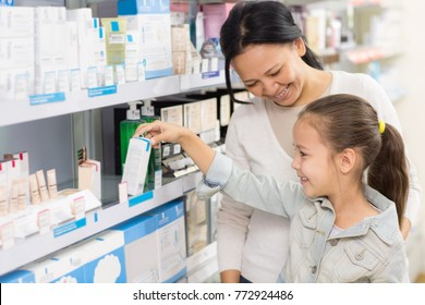 Cheerful mature Asian woman smiling at her beautiful young daughter while buying vitamins at the local drugstore love family motherhood children healthcare vitality parenting choice shopping ethnic