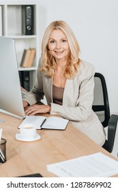 cheerful mature businesswoman using desktop computer and smiling at camera in office