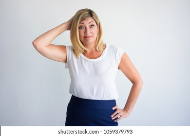 Cheerful mature Caucasian woman putting hands on head and thinking. Middle aged woman pretending supermodel and posing for fun. Decision making and humor concept