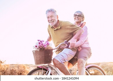 Cheerful mature couple of senior enjoy the outdoor leisure activity together riding a bike and laughing a lot - happy elderly active lifestyle with caucasian old people having fun