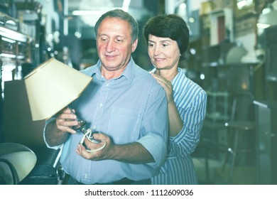 cheerful mature couple is shopping the old lamp for home in the antique store
