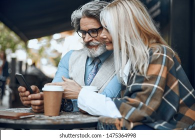 Cheerful mature couple sitting outdoors and looking at the smartphone screen