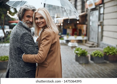 Cheerful mature couple turning and smiling under transparent umbrella. Website banner