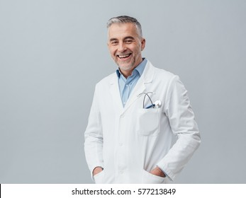 Cheerful mature doctor posing and smiling at camera, healthcare and medicine
