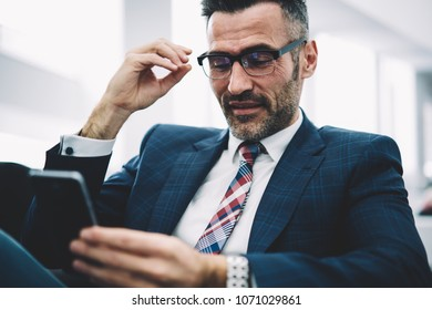 Cheerful mature entrepreneur reading funny notification on smartphone device sitting in office.Successful proud ceo in formal wear chatting online on telephone device via 4G internet connection