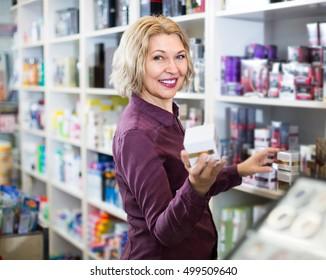 Cheerful mature european woman choosing face cream and smiling