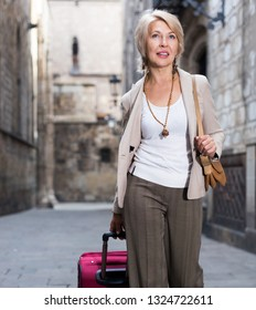 Cheerful mature female is walking with suitcase on the street outdoor.