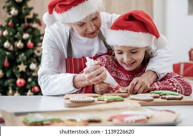 Cheerful mature grandmother is teaching her grandchild how to decorate Christmas cookies. Girl is watching process with interest and smiling