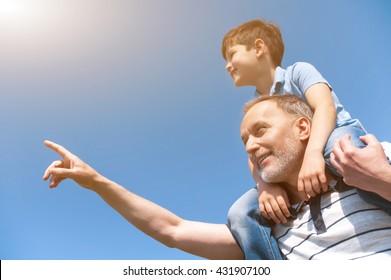 Cheerful mature grandparent is teaching his grandchild