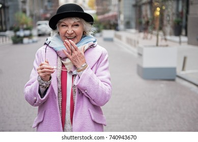 Cheerful mature lady smiling during walk in city