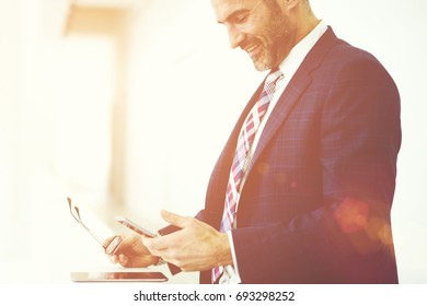 Cheerful mature male executive checking email box on smartphone receiving feedback from business colleagues,positive CEO reading news browsing information via mobile standing on promotional background