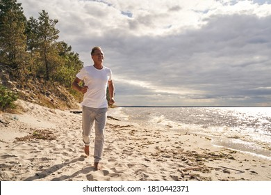 Cheerful mature male is warming up in morning by jogging before workout in sunny beach