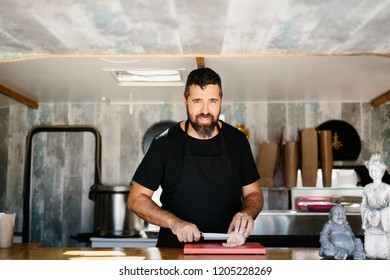 Cheerful mature man in apron standing in food truck cutting fish liver and smiling at camera working as street food vendor