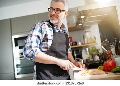 Cheerful mature man in kitchen preparing dish