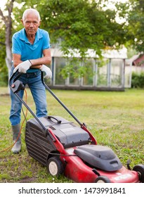 Cheerful mature man with lawnmower on a farm