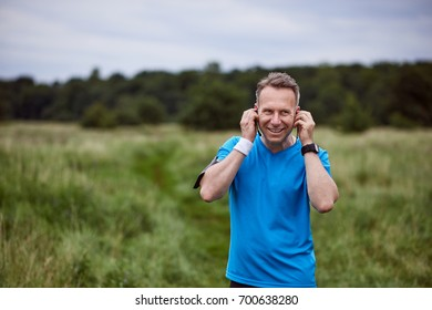 Cheerful mature man listening to music while walking outdoors