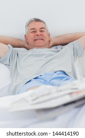 Cheerful mature man relaxing in bed