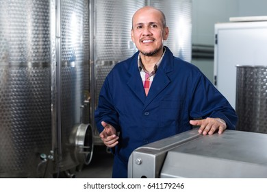 Cheerful mature man in uniform working in wine secondary fermentation section