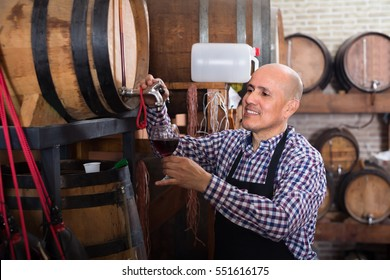Cheerful  mature seller pouring wine from wood barrel  in wine house