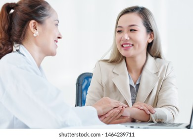 Cheerful mature Vietnamese doctor congratulating young female patient with recovery