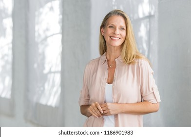 Cheerful mature woman in casual looking away indoor. Successful senior woman smiling and standing confidently. Portrait of happy beautiful lady in a pink shirt with toothy smile standing.