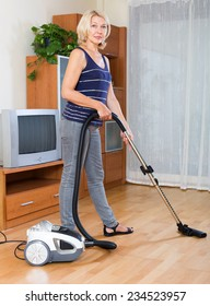 cheerful  mature woman cleaning with vacuum cleaner on parquet floor at home