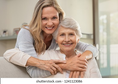 Cheerful mature woman embracing senior mother at home and looking at camera. Portrait of elderly mother and middle aged daughter smiling together. Happy daughter embracing from behind elderly mom.