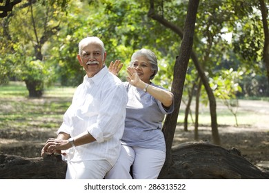 Cheerful mature woman and man having fun while sitting on tree trunk in park