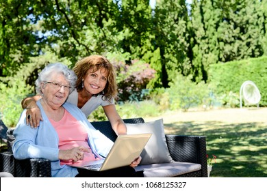cheerful mature woman with mother elderly senior female sitting outdoor and playing with a laptop computer in retirement house hospital garden